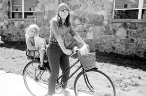 "Mary Hayes on a bike, with her young daughter Jess Bates on the back. She is distributing her cookbook, ""Aspen Potpouri"", September 1968. She is next to the Post Office on Spring Street."